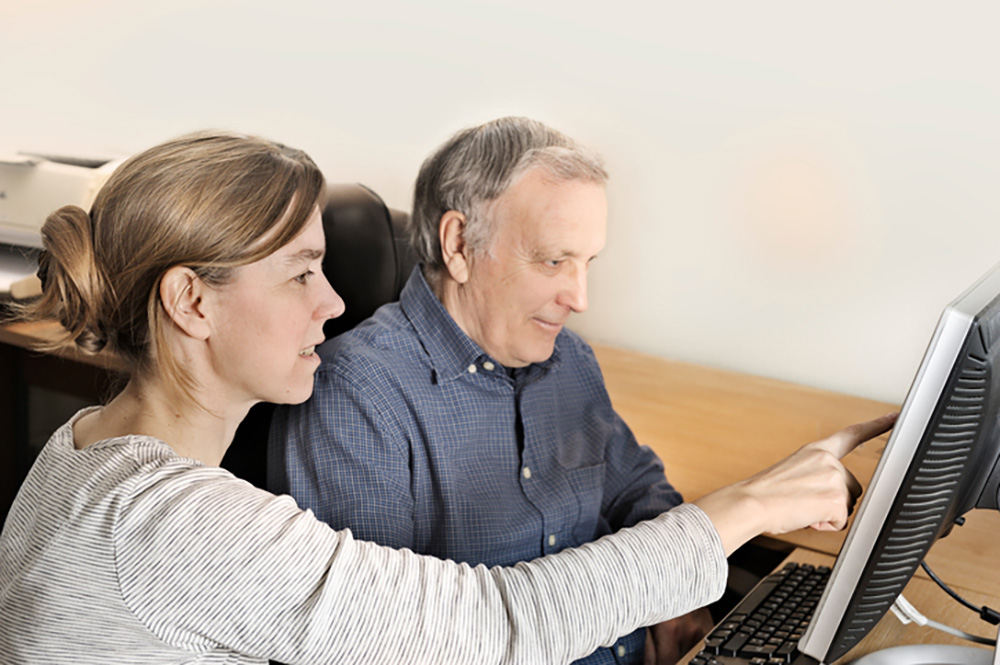 Daughter showing her father a list of common scams to beware of heading into tax season on a computer
