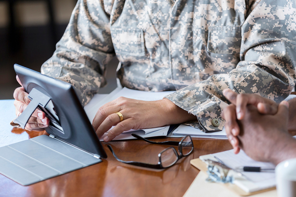 Tax help for military officer shown meeting with an accountant about IRS tax problems in military household